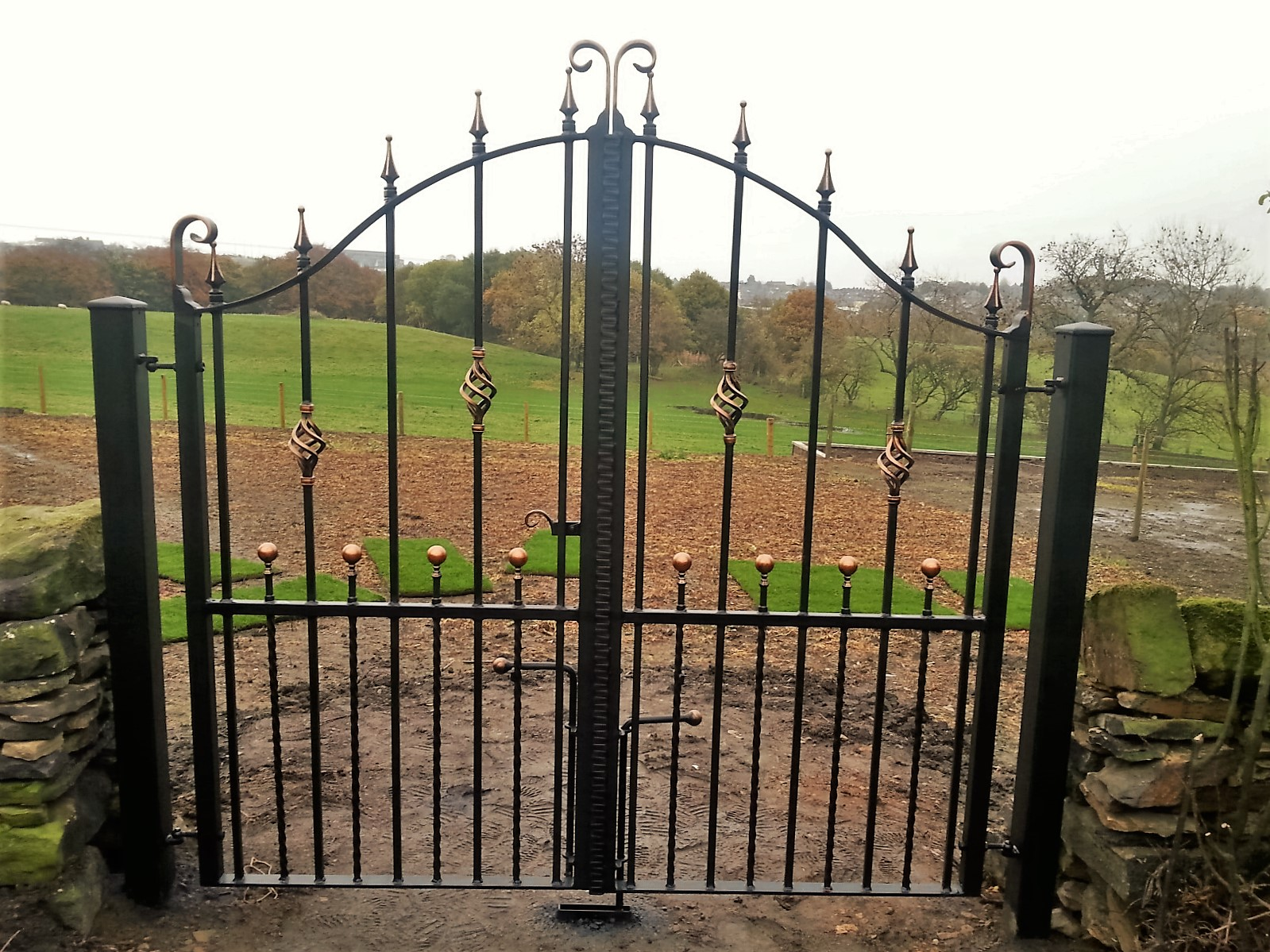 Wrought_iron_driveway_gates_copper_patina_bowtop